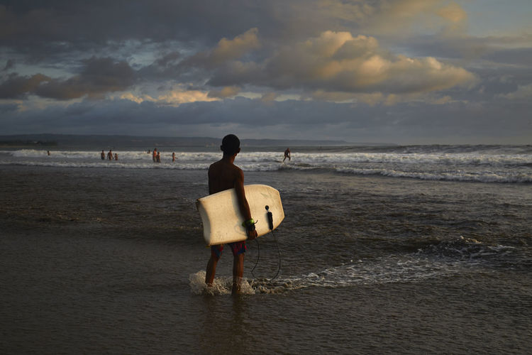 Local surfer with his boogie board checking out the waves Bali Beach Boogie Board Cloud Cloud - Sky Clouds And Sky Dramatic Sky Dramatic Sunset Full Length Getting Away From It All Horizon Over Water Kuta Beach Men Ocean Ocean Sea Rear View Remote Sea Shore Sky Surfer Tranquil Scene Tranquility Vacations Wave