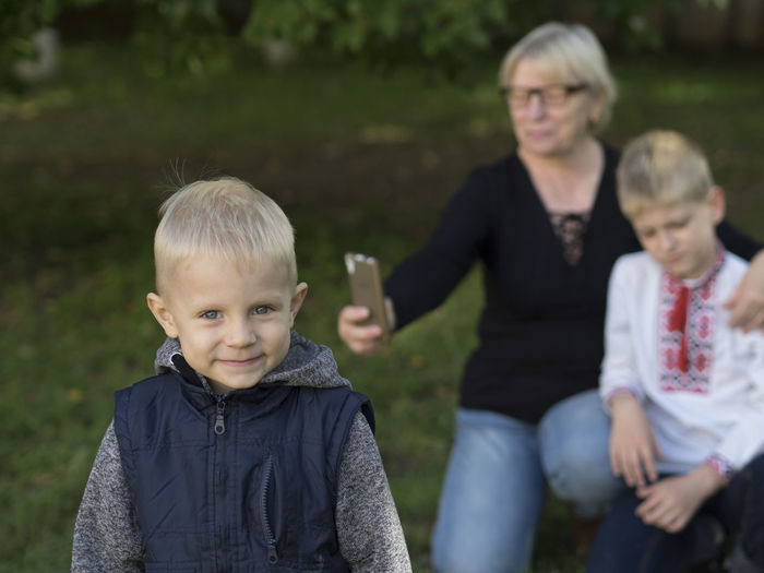 Portrait Of Boy With Brother And Grandmother At Park