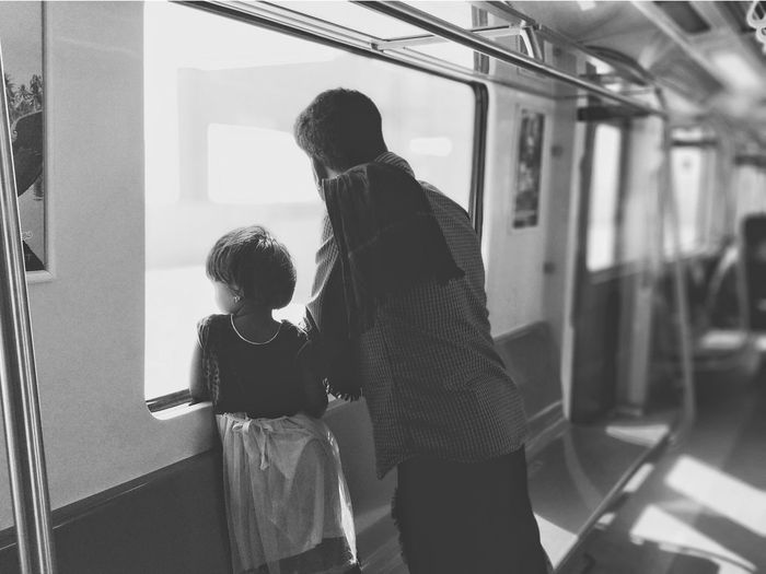 Rear View Of Man And Girl Looking Through Window In Train