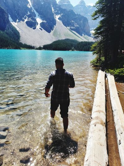 Rear view of man on lake against mountains