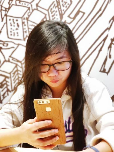 Young woman using smart phone while sitting against wall in cafe