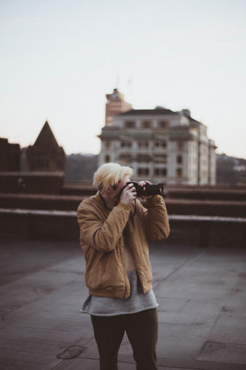 Woman Photographing While Standing On Street