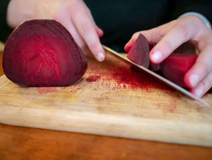 Cropped hands of person cutting common beet in kitchen