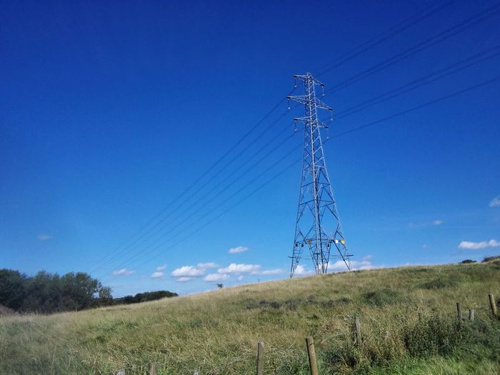 Low angle view of electricity pylon on field against blue sky