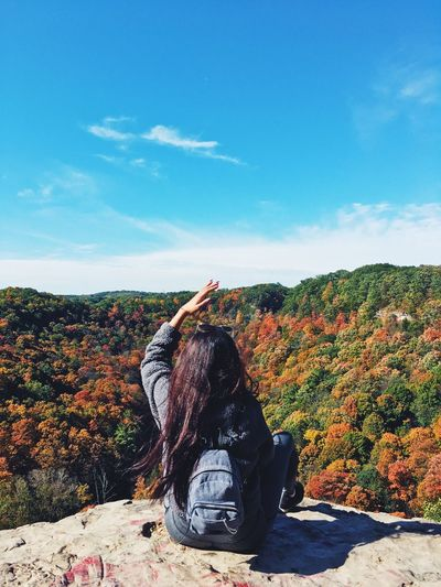 Rear view of woman sitting on autumn leaves against sky