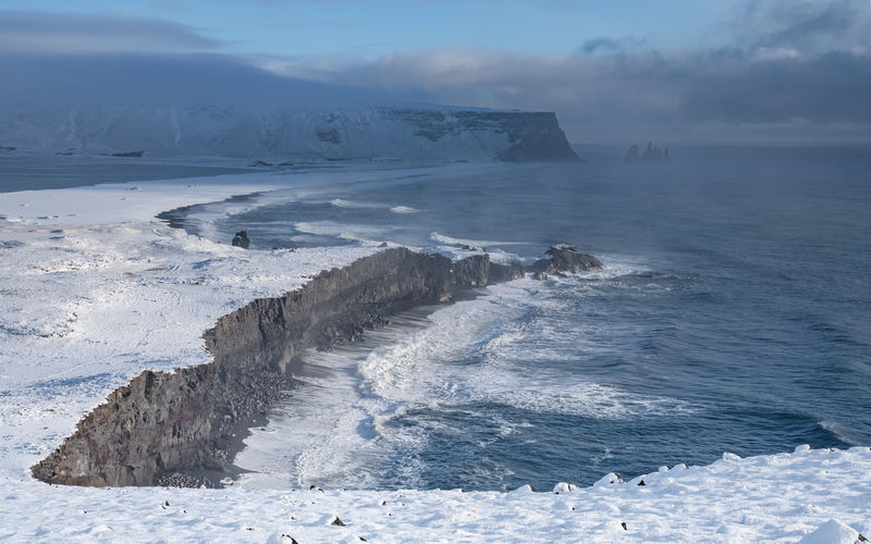 Panoramic image of the coastal landscape of Cape Dyrholaey on a winter day with snow-covered coastline, Iceland Beauty In Nature Water Scenics - Nature Sky Tranquil Scene Tranquility Nature Sea Land No People Non-urban Scene Idyllic Cape Dyrholaey Dyrhólaey Iceland Coast Coastline Coastal Feature Travel Travel Destinations Tourism Landscape Nature Ecosystem  Cliff Panorama Scenics Scenery Europe