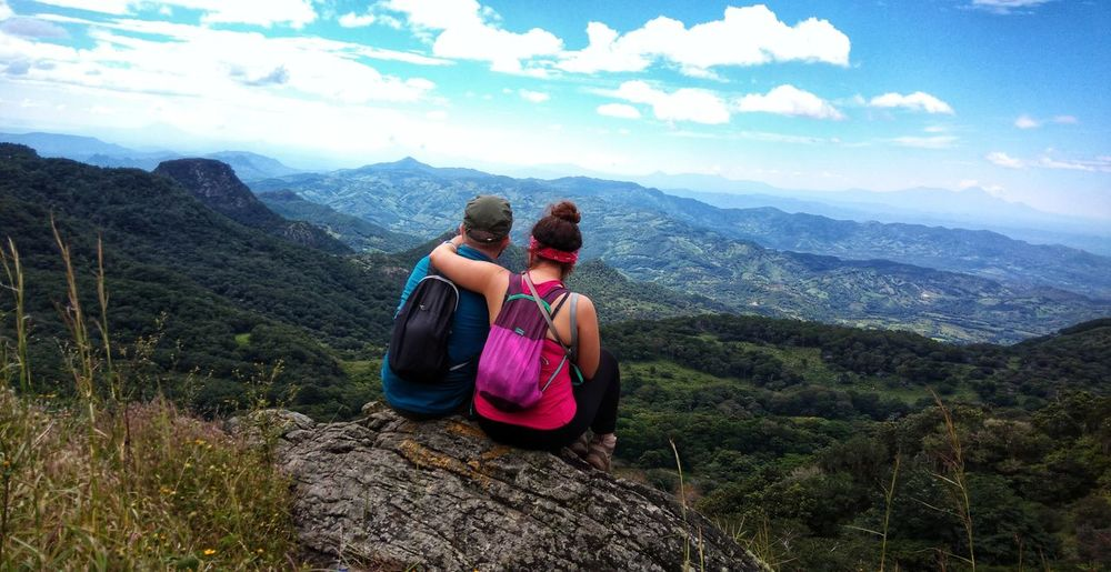 Rear view of couple sitting on rock against sky