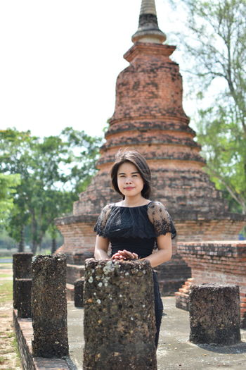 Portrait of young woman standing against old ruin temple
