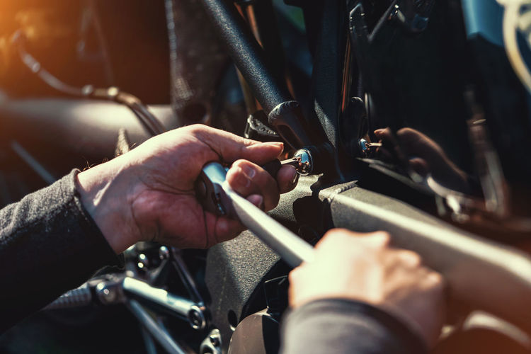 Cropped hands of mechanic repairing motorcycle