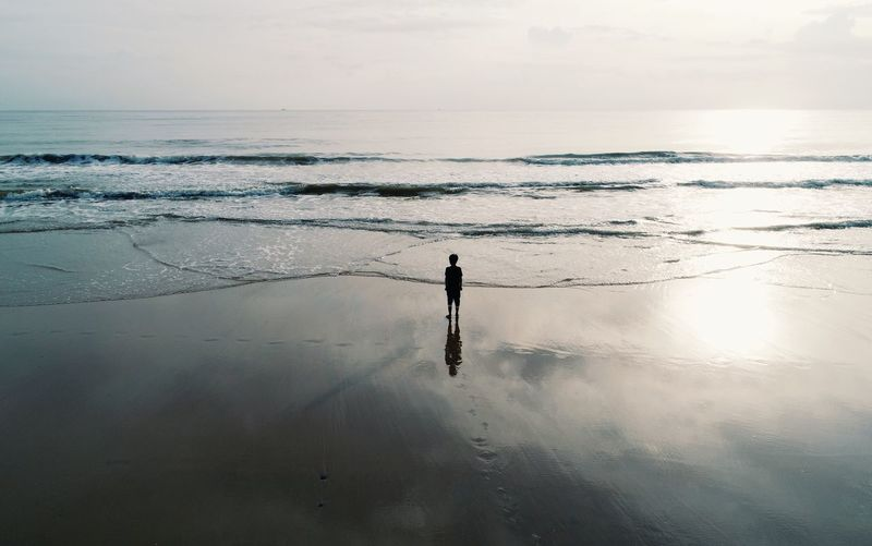 Rear view of boy standing at sea shore