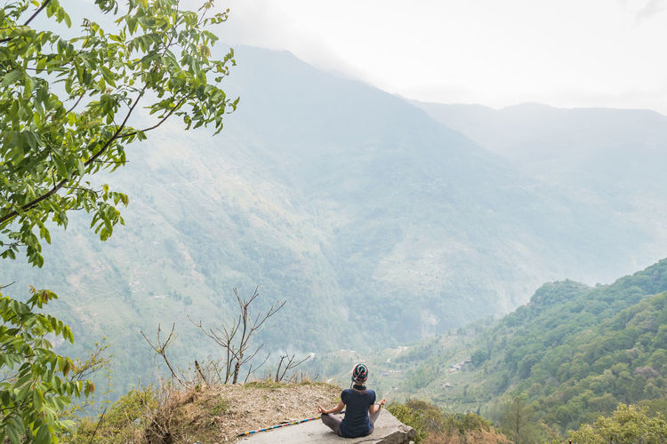 Rear View Of Woman Practicing Yoga Against Mountain