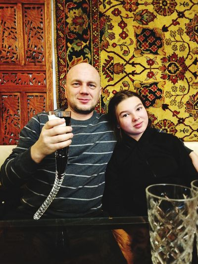 Portrait of young woman with man holding wineglass while sitting at restaurant