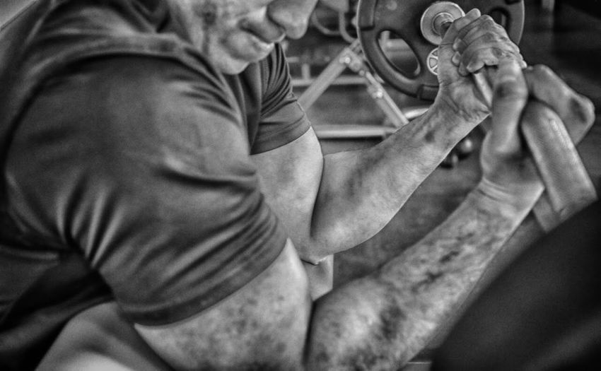 Man Holding Barbell Curl In Gym