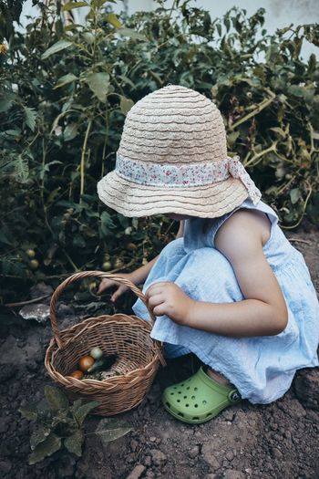 Full length of girl crouching by wicker basket and plants