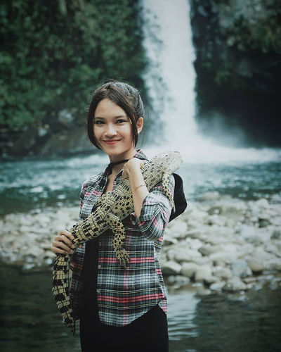 Portrait of smiling young woman holding crocodile against waterfall