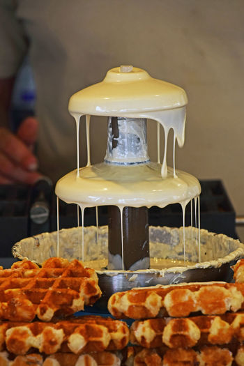 Close-up of white chocolate fountain by waffles at table