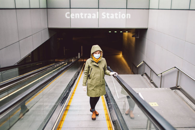 Portrait of woman wearing mask standing on escalator at subway station