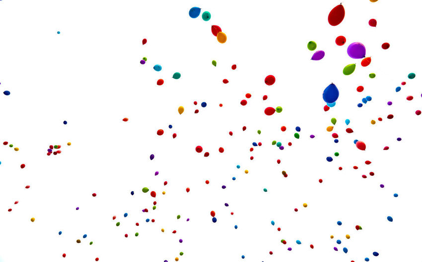 Multi colored balloons against white background