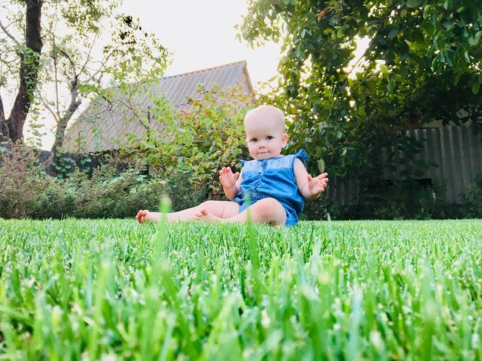 Portrait of cute baby girl sitting on field