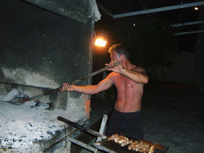 Shirtless man working in kitchen