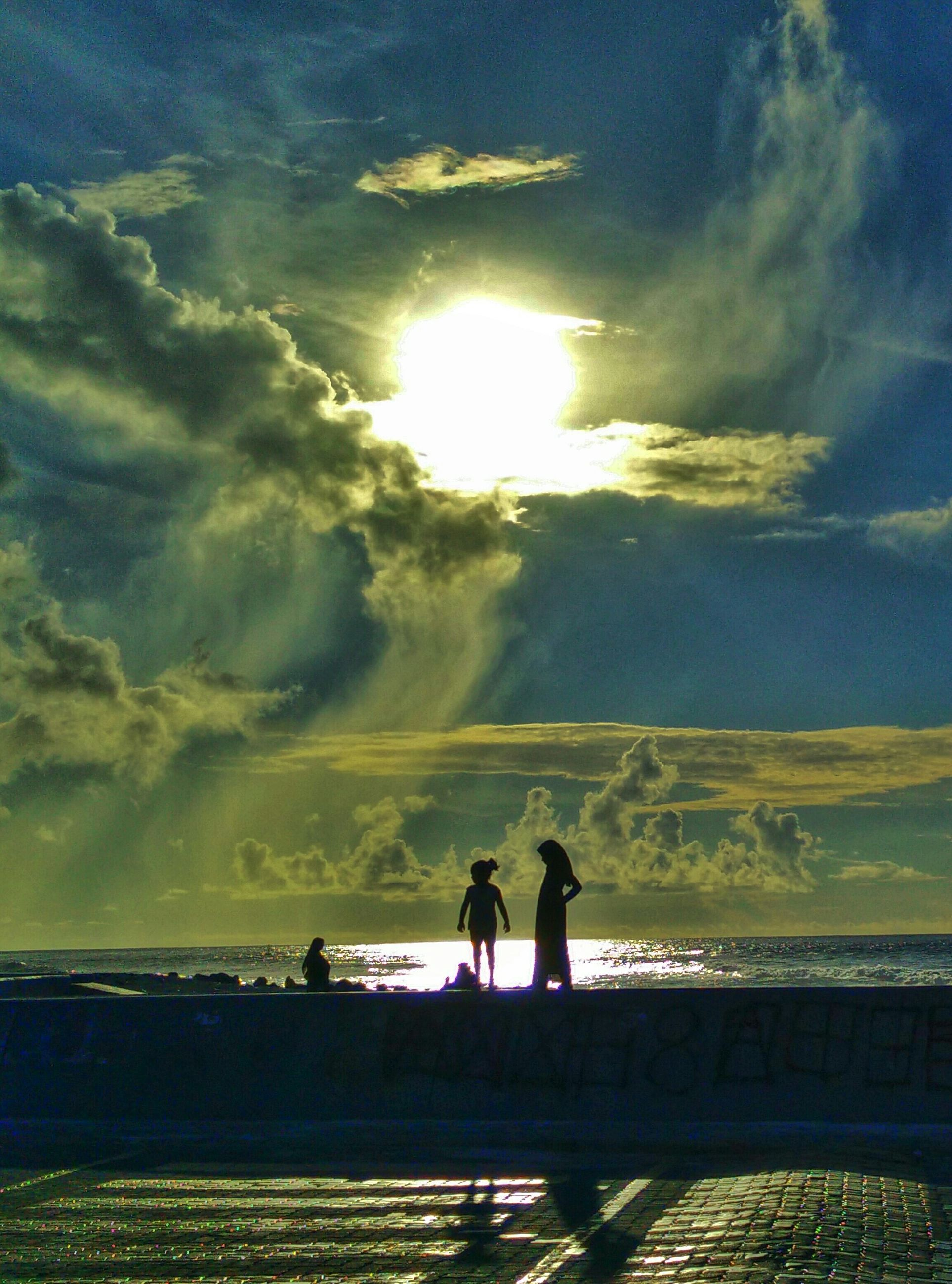 sky, lifestyles, leisure activity, silhouette, sunset, men, togetherness, cloud - sky, tranquil scene, standing, water, tranquility, beauty in nature, scenics, nature, rear view, bonding, person