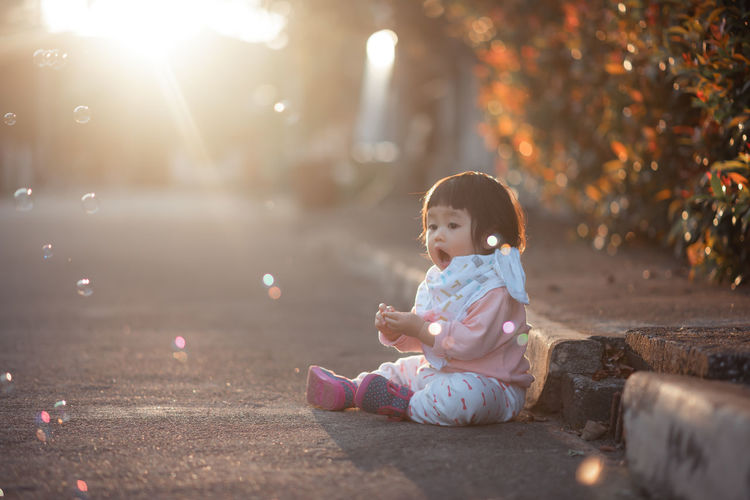 Cute girl looking at bubbles while sitting on road