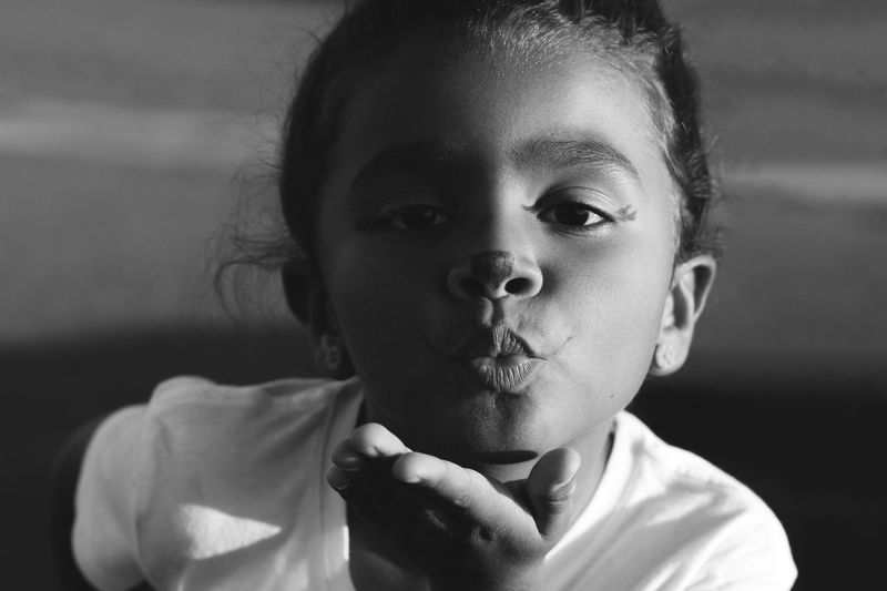 Close-Up Portrait Of Girl Blowing Kiss