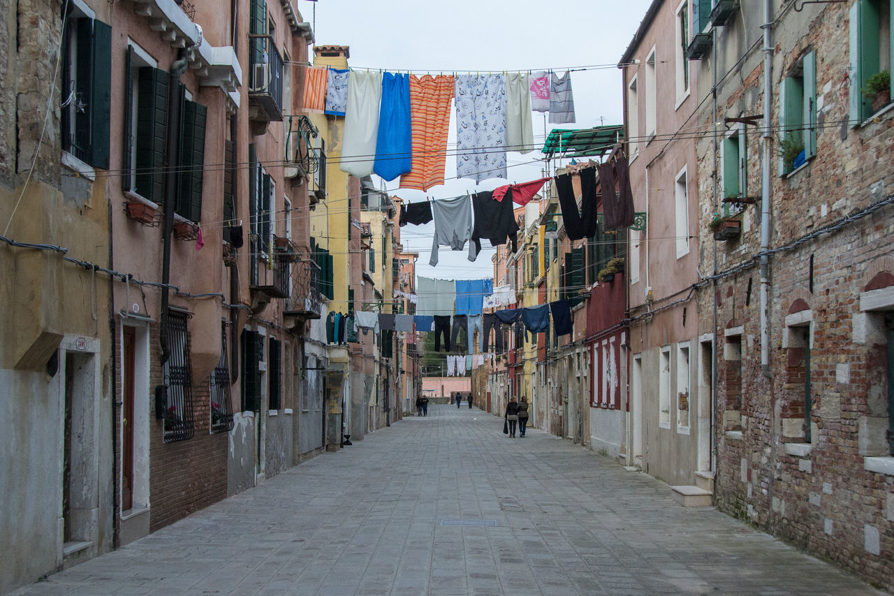 Laundries Hanging On Clothesline Above Street Amidst Building