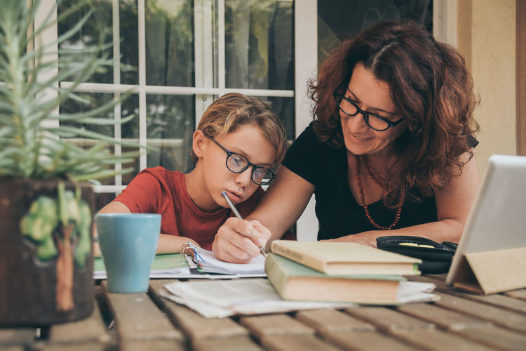 Mature woman helping son with studies at home