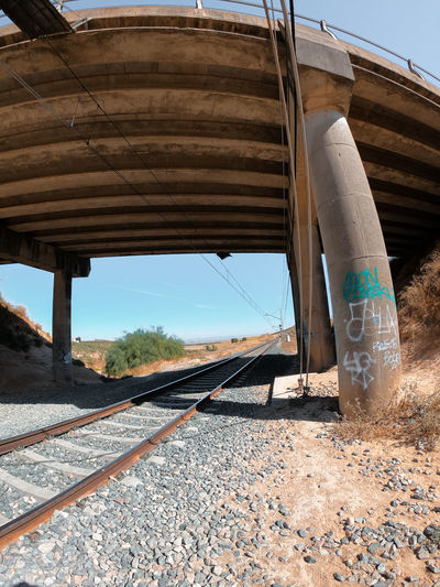Railroad tracks by road against sky