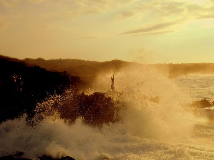 Waves Splashing At Rocky Shore Against Cloudy Sky During Sunset