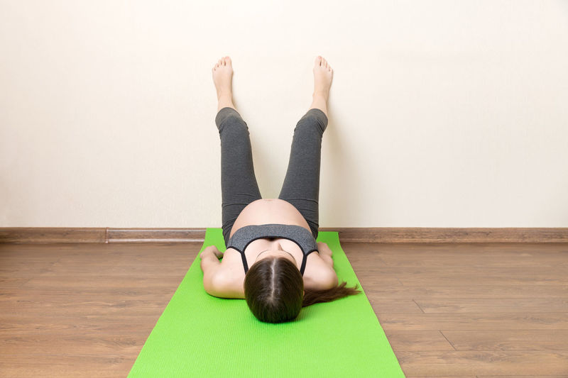 Low section of woman relaxing on hardwood floor
