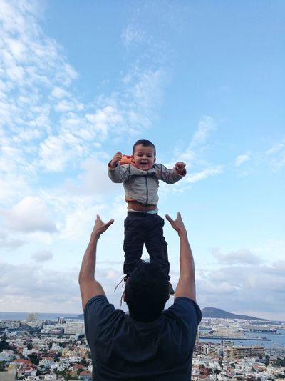 Rear view of playful father throwing son in air against sky