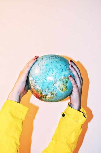 Cropped hands holding globe against wall