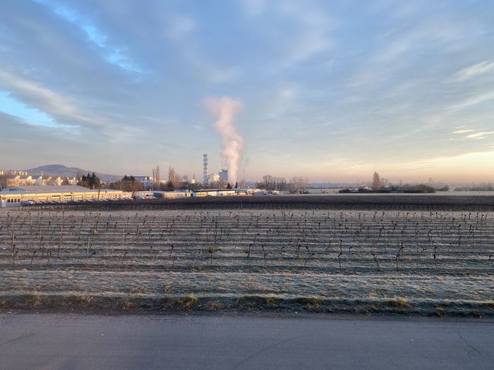 Smoke emitting from factory against sky during winter