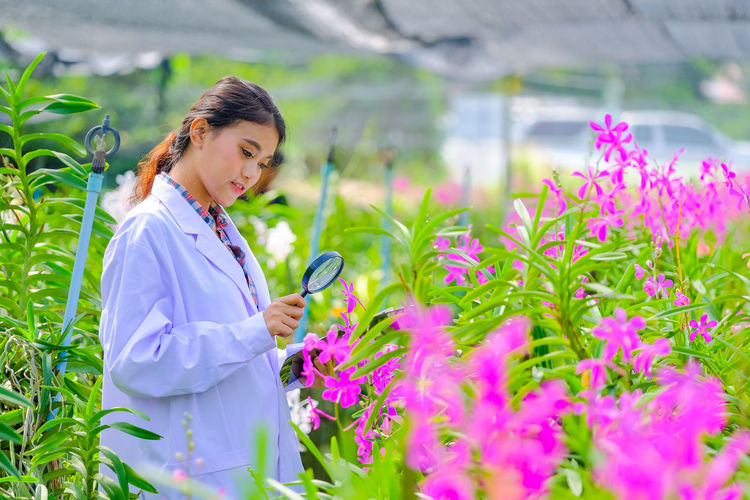 Woman holding flowering plants in greenhouse
