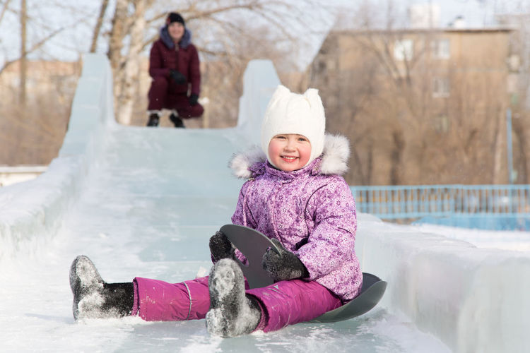 Portrait smiling girl with sled sitting on slide snow during winter