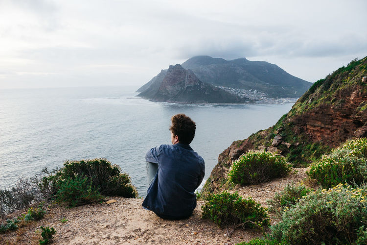 Man looking at mountains by sea against sky