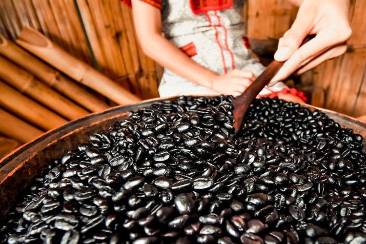 Midsection of woman holding coffee bean