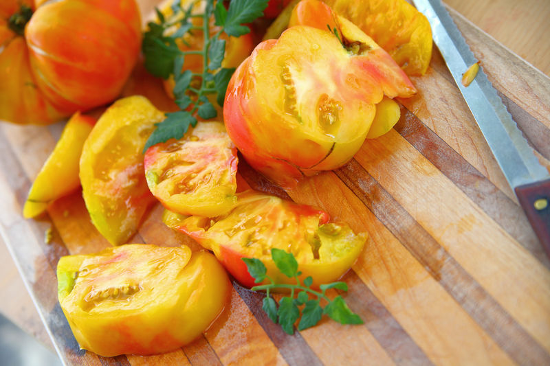Preparing fresh heirloom tomatoes Food Healthy Eating Freshness Close-up Vegetable Cutting Board No People Indoors  Wood - Material Food Preparation Kitchen Knife Vegan Vegetarian Food Fresh Produce Colorful Natural Light Textures Summer Seasonal Room For Text Copy Space