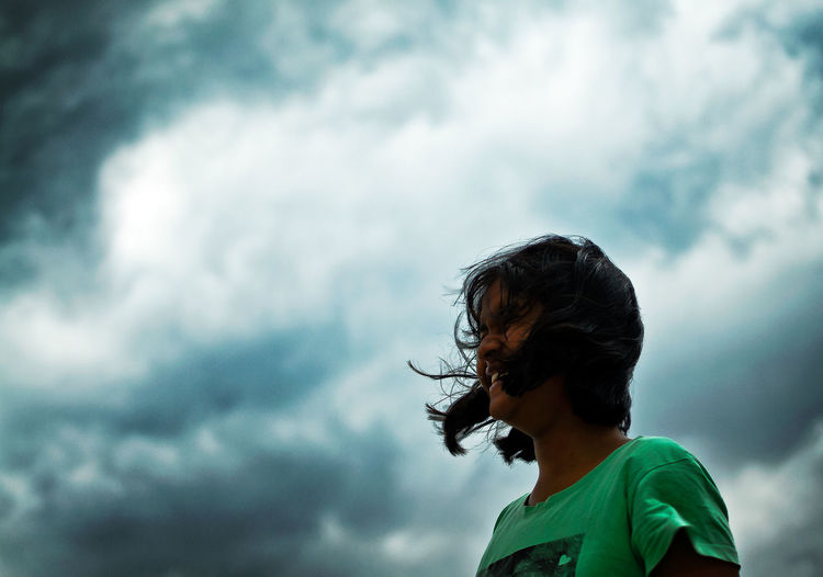 Low Angle View Of Teenage Girl With Tousled Hair Standing Against Cloudy Sky