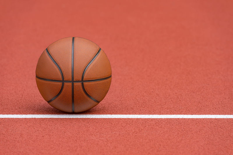 Close-up of basketball hoop against red background