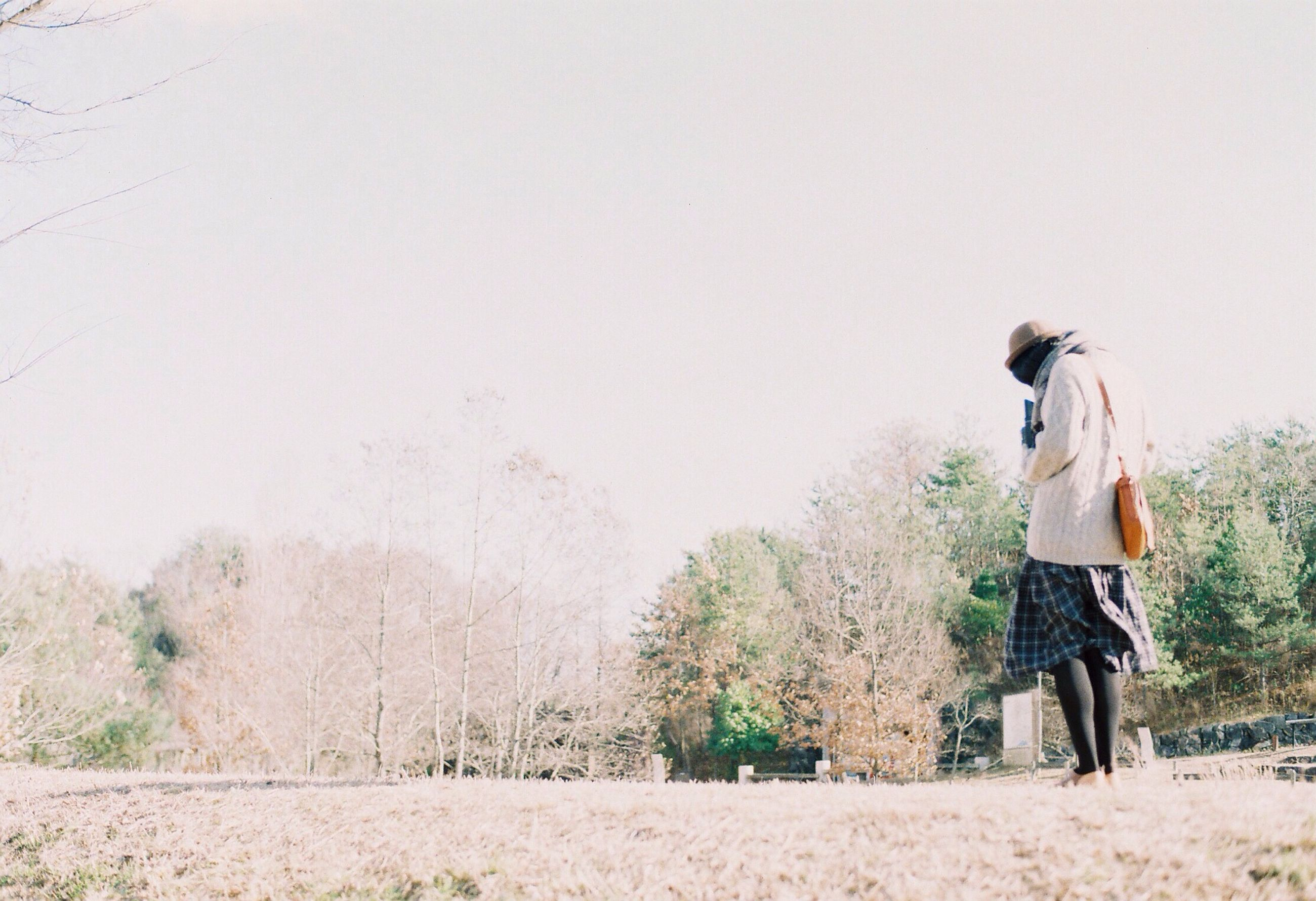 lifestyles, leisure activity, full length, casual clothing, rear view, tree, standing, clear sky, men, copy space, nature, tranquility, tranquil scene, walking, person, landscape, day