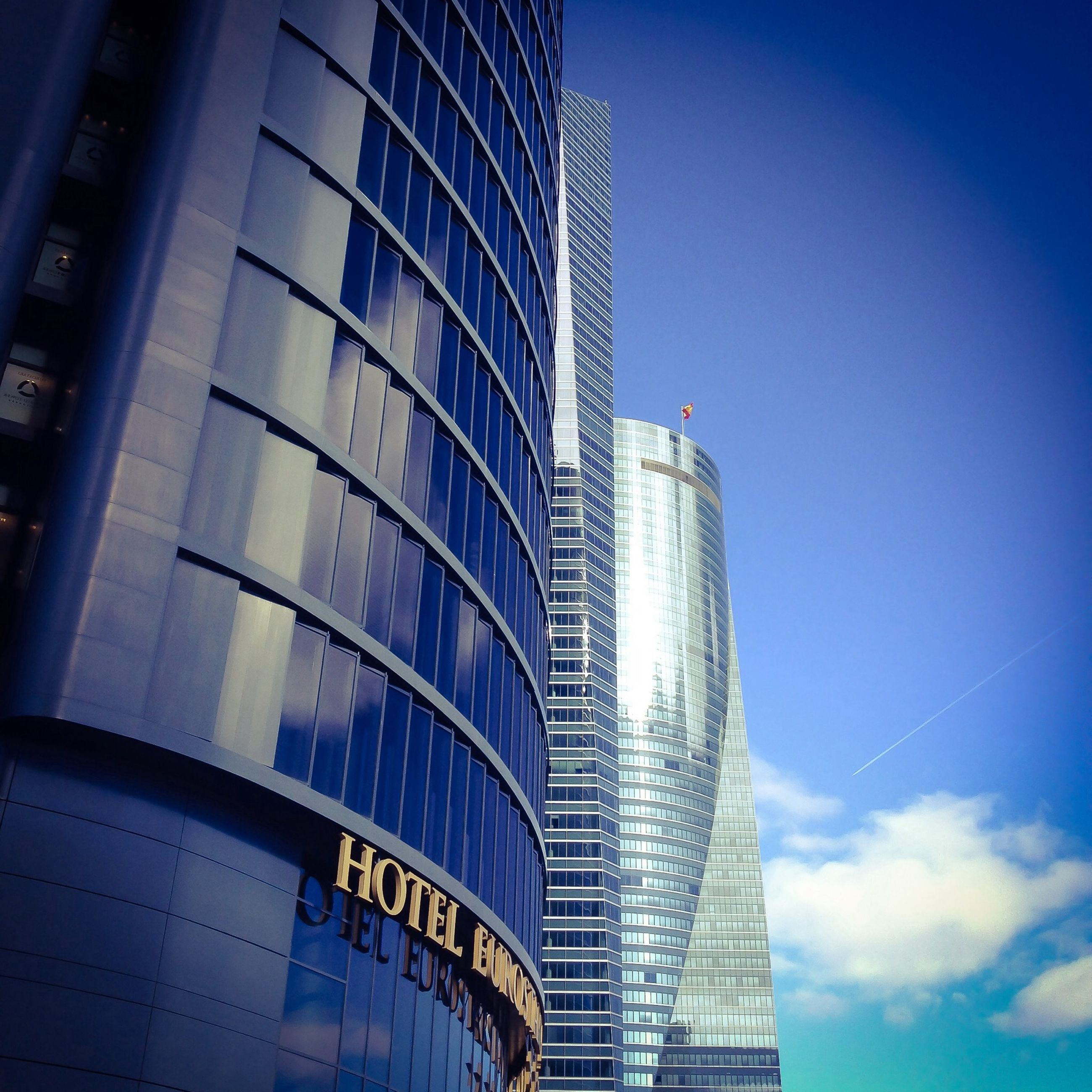 architecture, building exterior, built structure, low angle view, modern, office building, city, skyscraper, blue, tall - high, building, tower, sky, reflection, glass - material, tall, clear sky, day, outdoors, no people