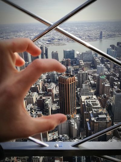 Close-up of hand holding cityscape against sky