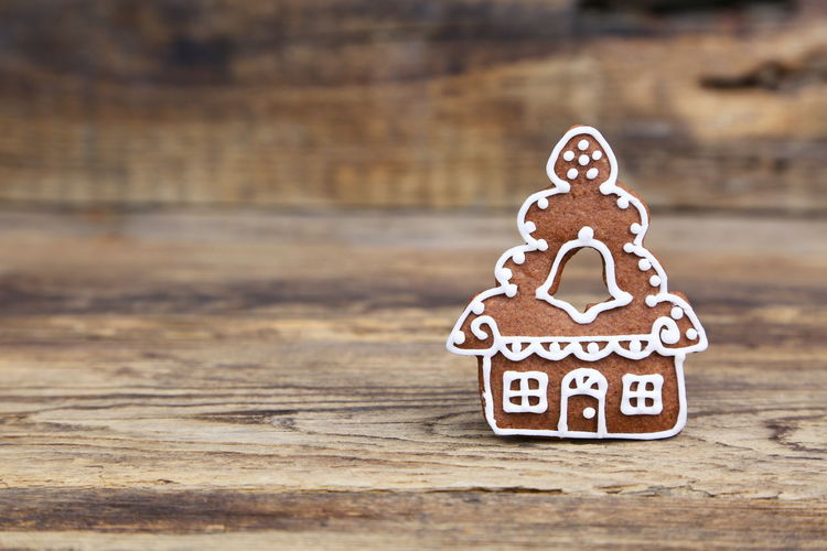 Close-up of house shaped gingerbread cookie on wooden table