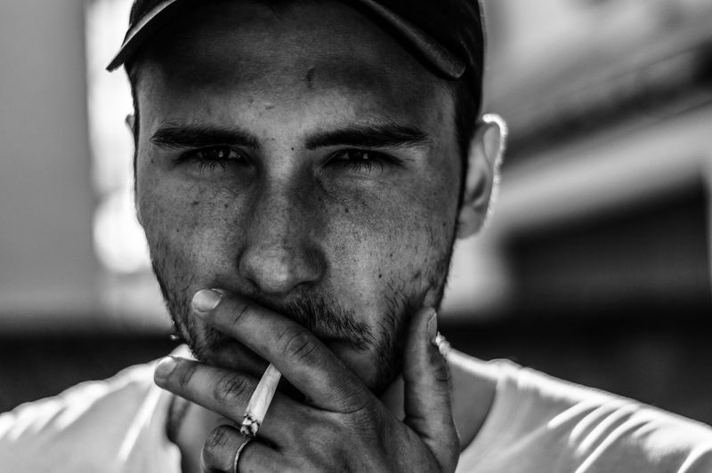 Close-Up Portrait Of Young Man Smoking Cigarette