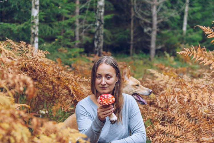 Woman holding mushroom while sitting by dog in forest