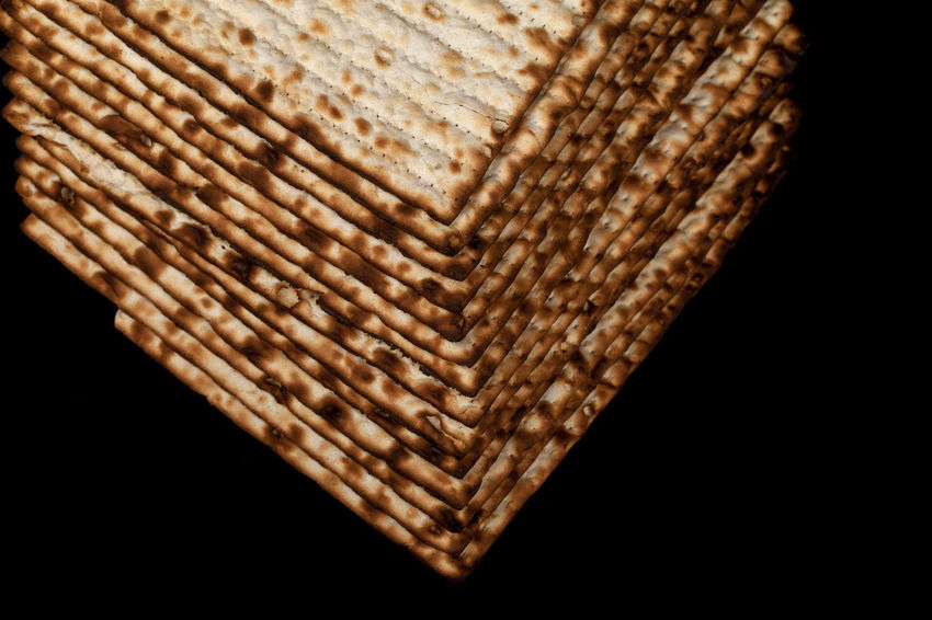 Traditional Jewish matzah on a black background. Close-up Passover Art And Craft Basket Black Black Background Bread Brown Close-up Container Creativity Cut Out Design Food And Drink Indoors  Kosher Luxury Matza Matzah Matzo Matzoth No People Pattern Pesach Religion Single Object Snack Still Life Studio Shot Textured  Wicker Wood - Material