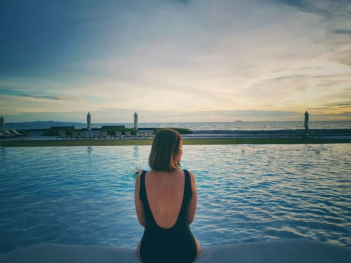 Rear view of woman looking away while sitting by swimming pool at sunset